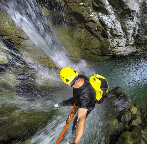 Canyoneering member with selfie stick rappeling down the waterfall in the canyon.